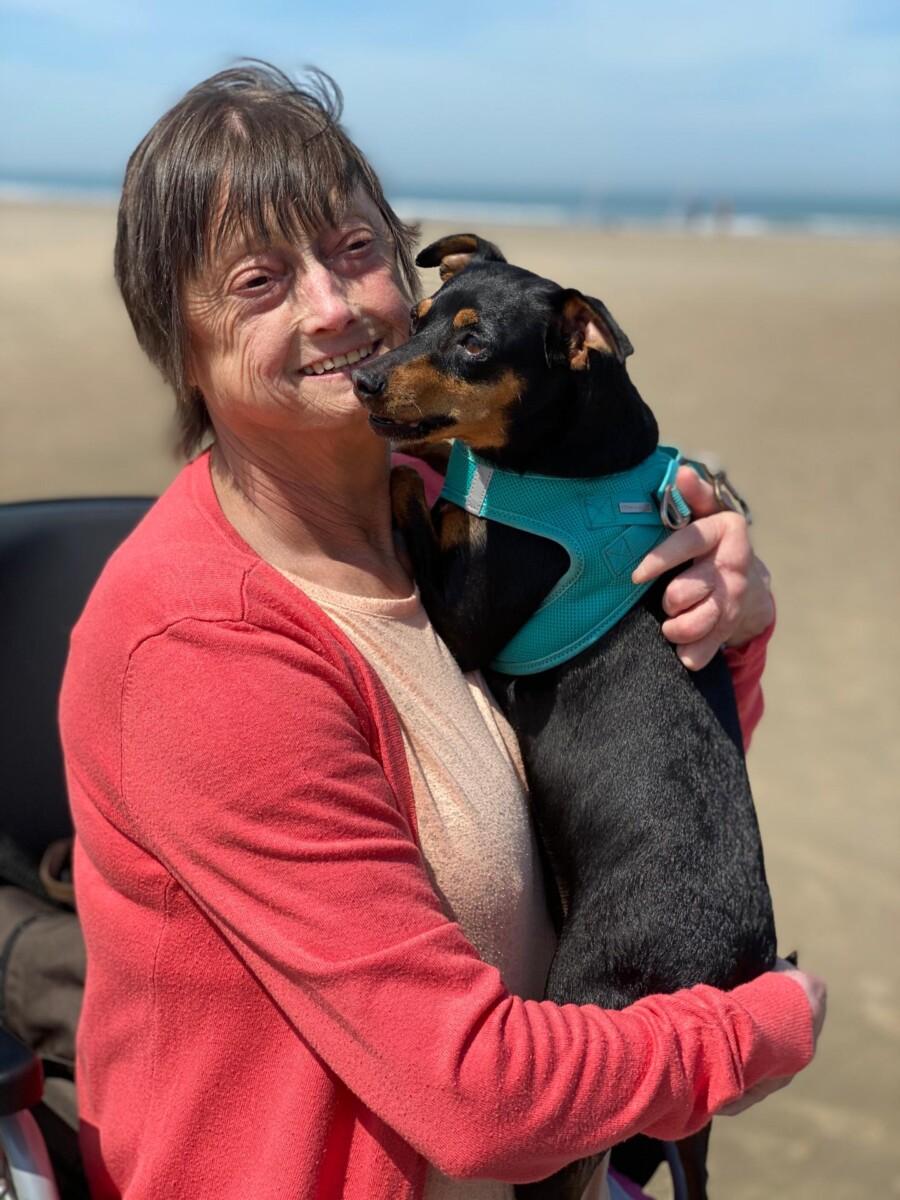 Mevrouw met hondje op strand