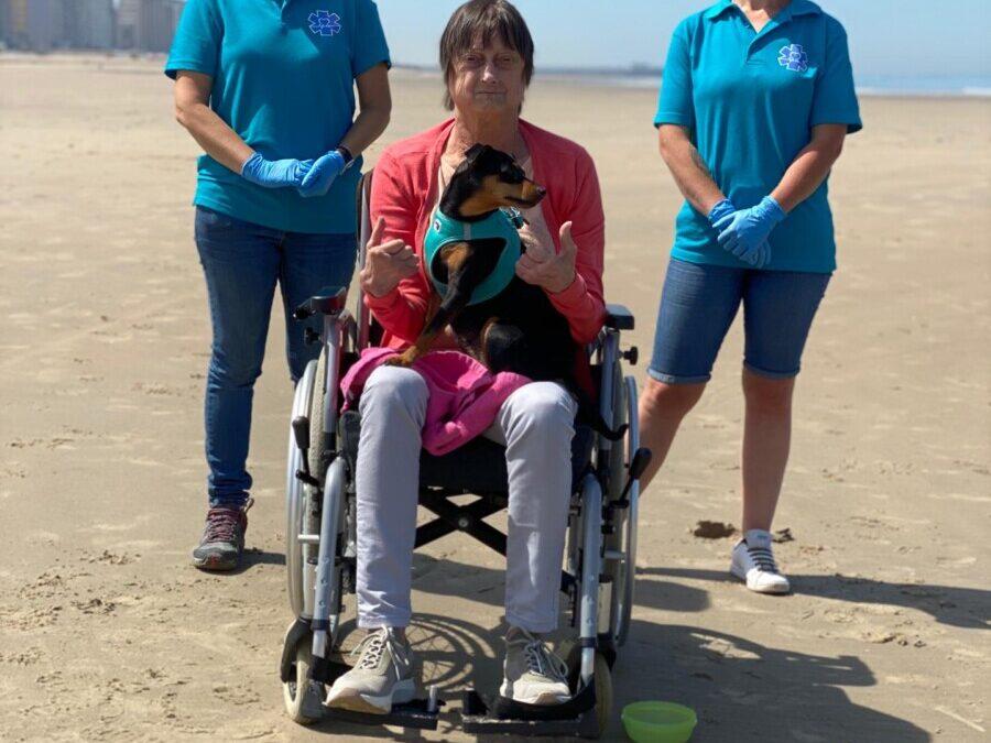 Wensambulance met mevrouw op strand met haar hondje